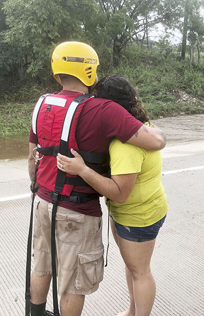 Luis Davila, Jr., and his wife Natalie embrace each other as they stand near the banks of the San Saba River after being rescued Friday, September 7, 2018, after their car was swept downstream by floodwaters crossing over FM 864 near Fort McKavett.   | COURTESY PHOTO